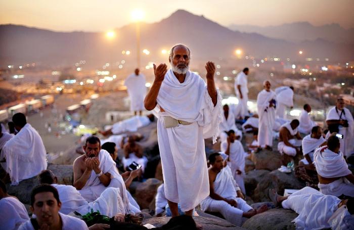 A Muslim pilgrim prays atop Mount Mercy on the plains of Arafat